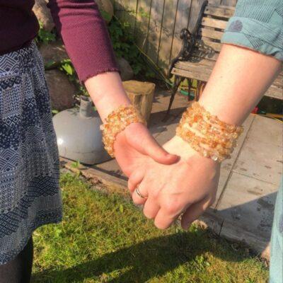 To der holder i hånd med brændt citrin armbånd på